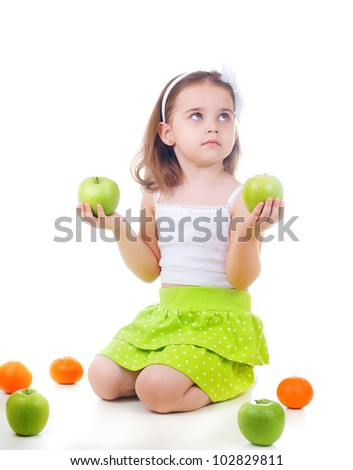 Little smiling girl holding green apples and looking up on white background - stock photo