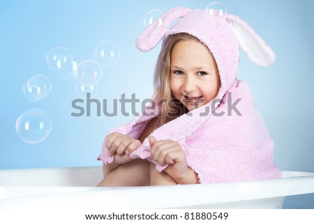 Little smiling girl in a bath on blue background - stock photo