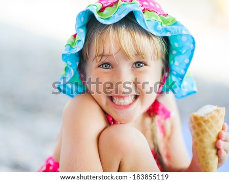 little smiling girl in a hat with ice cream - stock photo