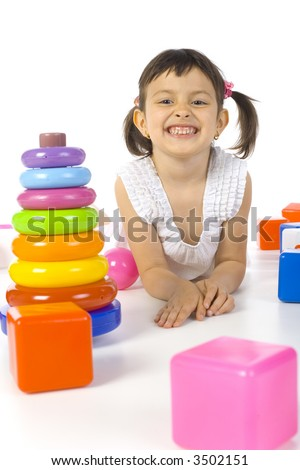 Little smiling girl lying between colored rings and blocks. Looking at camera. White background - stock photo