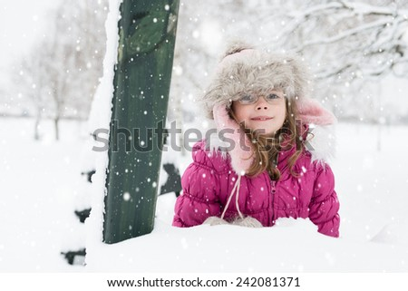 Little, smiling girl lying in a snow and looking at camera, winter landscape - stock photo
