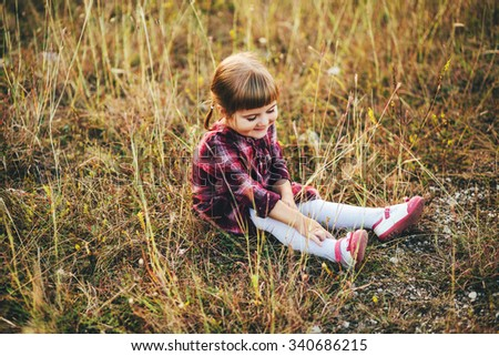 Little smiling girl lying on her back in a field top view - stock photo