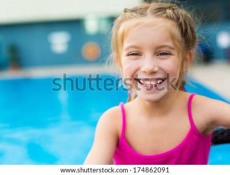 little smiling girl near a swimming pool