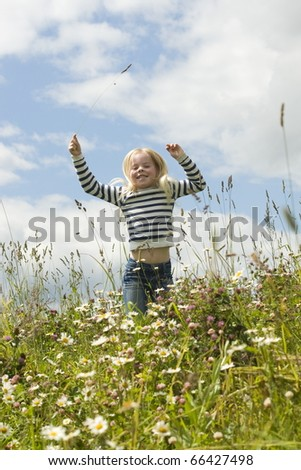 little smiling girl on meadow - stock photo
