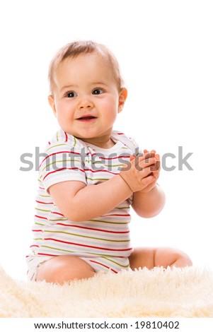 Little smiling girl on sheepskin - stock photo