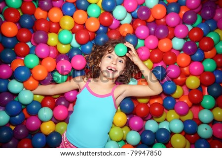 little smiling girl playing lying in colorful balls park playground - stock photo