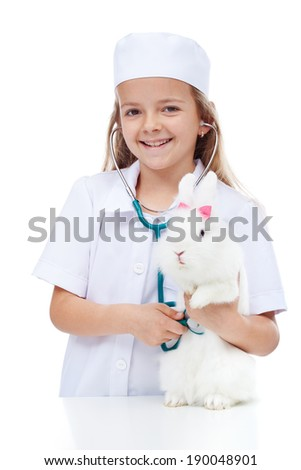 Little smiling girl playing veterinary with her rabbit - listening with a stethoscope - stock photo
