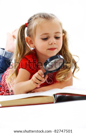Little smiling girl reading a book with a magnifying glass - stock photo