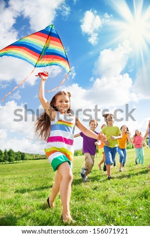 Little smiling girl running with kite and her happy friends together in the park