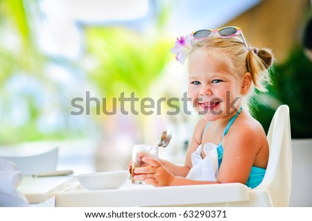 little smiling girl sits in baby-chair and have a breakfast