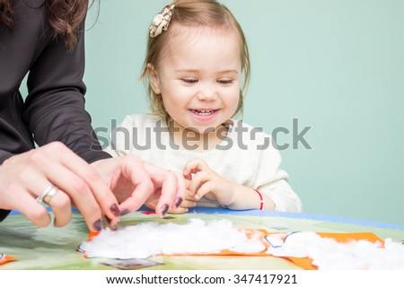 Little smiling girl sitting at the table, make things with hands - stock photo