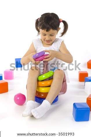 Little smiling girl sitting on the floor and playing with colored rings. Whole body, white background