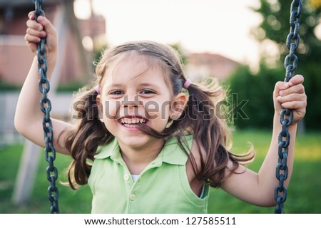 Little smiling girl swinging close up portrait. - stock photo