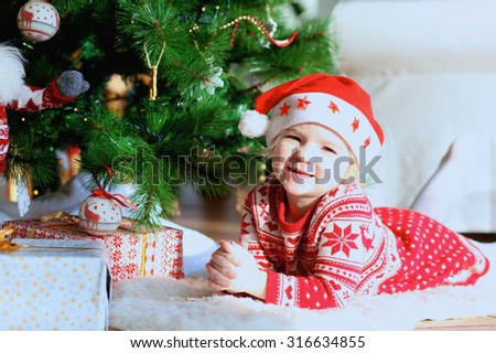 Little smiling girl wearing Santa hat and festive dress lying on the lambskin carpet near the Christmas tree and gifts. Adorable kid making new year wishes. - stock photo