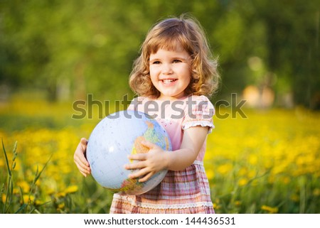 Little smiling girl with a globe in a summer field - stock photo