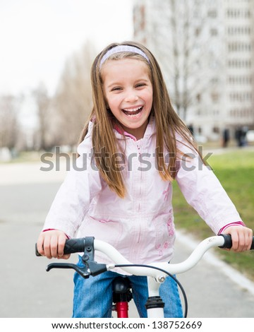 little smiling girl with bicycle on road - stock photo