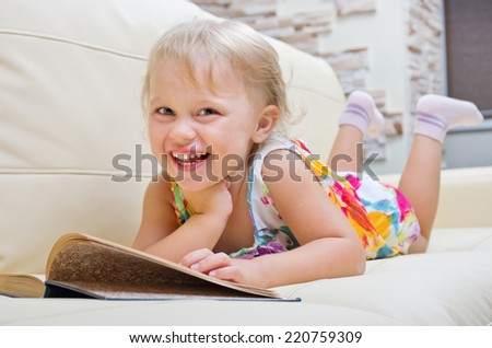 Little smiling girl with book on sofa - stock photo