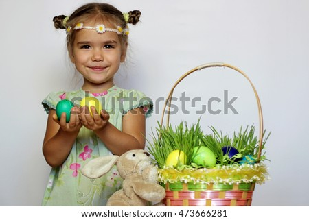 Little smiling girl with bunny and Easter basket with eggs decorated with the grass after egg hunt, happy family holiday