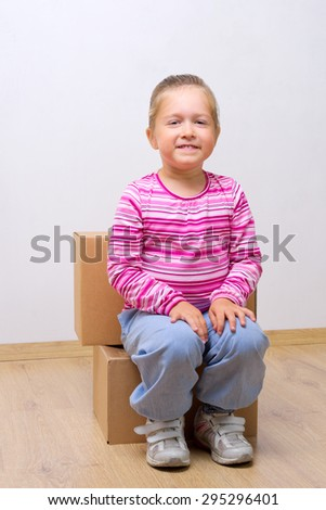 Little smiling girl with cardboard boxes - stock photo