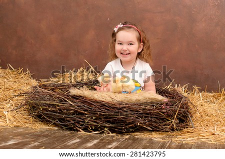 little smiling girl with chickens in nest indoors