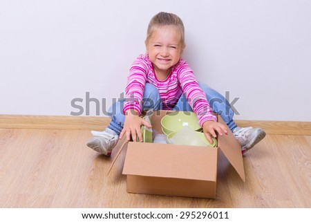 Little smiling girl with dishware - stock photo