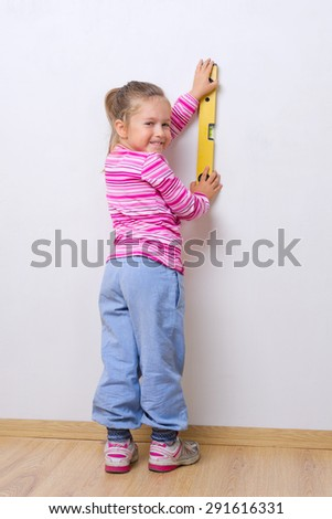 Little smiling girl with measuring level - stock photo