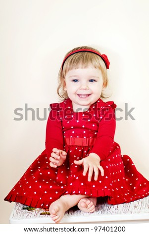 Little smiling girl with red dress - stock photo