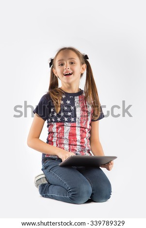 Little smiling girl with tablet on white background - stock photo