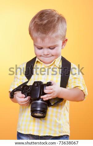Little smiling photographer watching photo on professional camera - stock photo