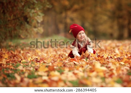 little smiling pretty girl with long blond hair in red hat and red dress sitting on the ground with yellow and gold leaves in the autumn park