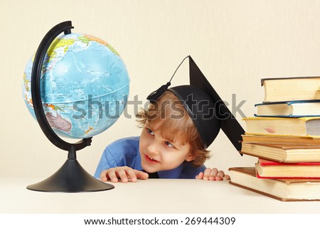 Little smiling professor in academic hat looks at a geographical globe  - stock photo
