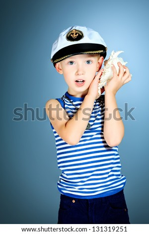 Little smiling sailor boy is listening to the sound of the sea in the shell. - stock photo