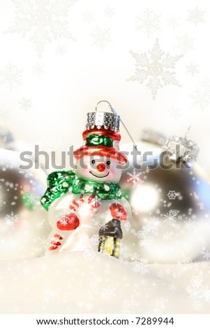 Little snowman ornament in the snow with white background - stock photo