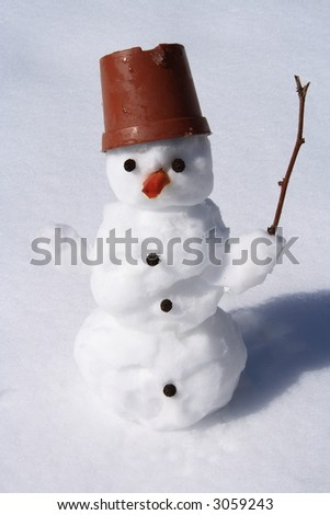 little snowman standing in the snow