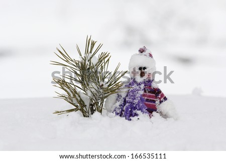 Little snowman toy in the snow - stock photo
