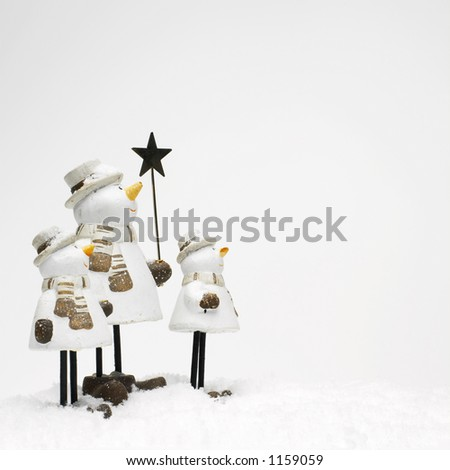 little snowmen standing in the snow (copy space) - stock photo