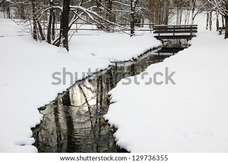 little snowy creek and bridge at winter time - stock photo