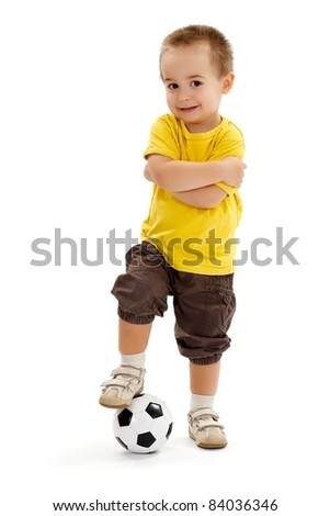 Little soccer player boy, holding his leg on ball, standing with arms folded - stock photo