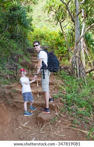little son and his father enjoying hike at kalalau trail at kauai island, hawaii - stock photo