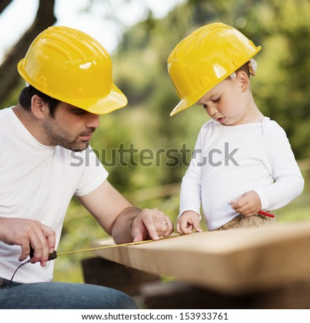 Little son helping his father with building work - stock photo