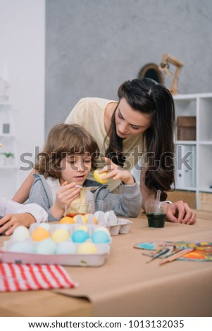 little son helping mother with eggs painting for easter holiday