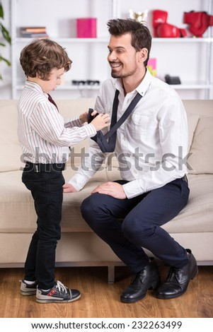 Little son is tying necktie to dad. Father is going to go to work. - stock photo