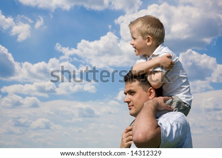 Little son sits on father`s shoulders outdoors - stock photo