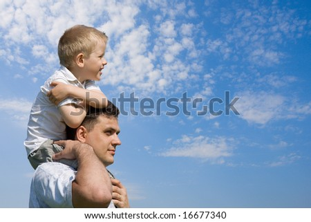 Little son sits on father`s shoulders outdoors