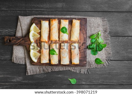 Little spring rolls on a cutting board on sacking on wooden black worn surface, lettuce, lemon slices, top view