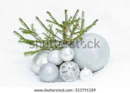 Little spruce tree on snowy ground with Christmas bauble ornaments at the bottom - stock photo