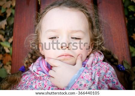 Little stubborn girl lying on the bench in the park - stock photo