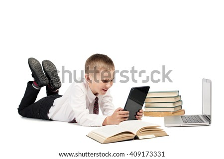 Little student Boy looking at tablet pc, lying with school books and laptop computer on White background isolated  - stock photo