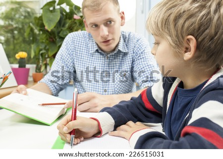 Little student doing homework with helpful father - stock photo