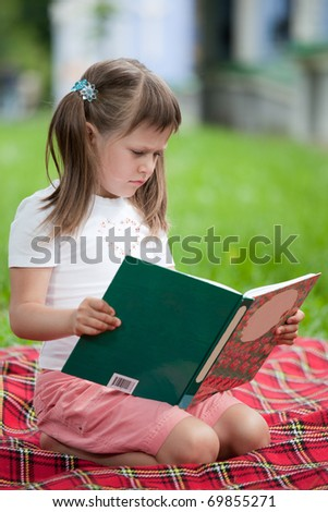 Little studious girl preschooler is reading open book and sitting on the red plaid on green grass in summer park - stock photo